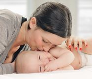 Mother kissing happy baby on cheek Royalty Free Stock Photo