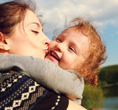 Mother kissing happy child outdoors summer backgro Royalty Free Stock Photos
