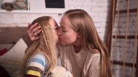 Mother kissing happy little daughter`s cheek stock video footage