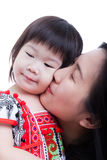 Mother kissing her adorable little daughter cheek, on white. Stock Photo