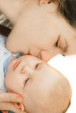 Mother kissing her baby. Over white Stock Photography