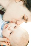 Mother kissing her baby. Over white Royalty Free Stock Photography