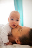Mother kissing her baby. Caring mother is kissing her baby boy on his cheek Stock Photography