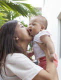 Mother kissing on her baby cheek use for motherhood and infant i Royalty Free Stock Photos