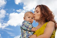 Mother kissing her baby on cloudy background Royalty Free Stock Image