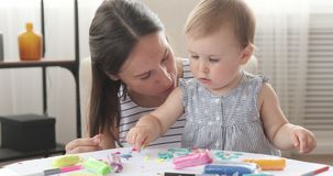 Mother kissing baby daughter while doing craft work. Mother kissing her baby daughter while playing with plasticine at home stock video footage