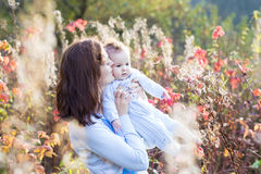Mother kissing her baby daughter on walk in autumn park. Young mother kissing her baby daughter on a walk in a sunny autumn park royalty free stock photo