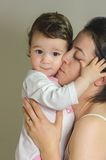mother kissing her baby girl Stock Images