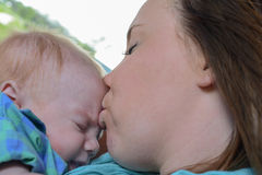 Mother kissing her baby Stock Images