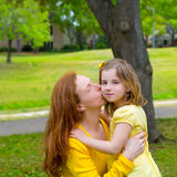 Mother kissing her blond daughter in green park. Outdoor dressed in yellow Stock Photos