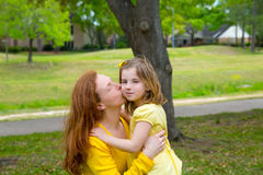 Mother kissing her blond daughter in green park Stock Images