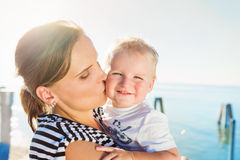 Mother kissing her boy, sunny summer by the water Stock Photo
