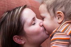 Mother kissing her child boy. Closeup of happy mother kissing her child boy Royalty Free Stock Images