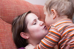 Mother kissing her child boy Stock Photography