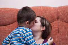 Mother kissing her child boy. Closeup of happy mother kissing her child boy Stock Images