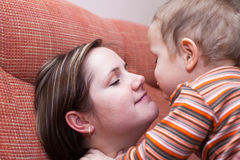 Mother kissing her child boy Stock Photos