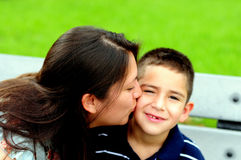 Mother kissing her child on the cheek. Mother kissing her young son on the cheek Stock Photo