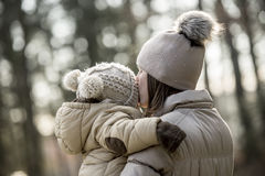Mother kissing her child outdoors. In the countryside in winter dressed in warm woolly hats Stock Image