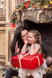 Mother kissing her cute little girl with Christmas gift near a fireplace with decorations Royalty Free Stock Photos
