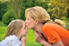 Mother is kissing her daughter Stock Photos