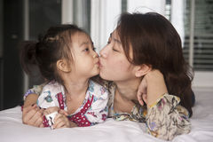 Mother kissing her daughter. Shot of an asian mother kissing her daughter Royalty Free Stock Images