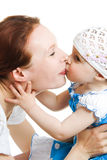 Mother kissing her daughter Stock Image