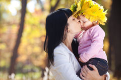 Mother kissing her daughter in autumn forest Stock Photography