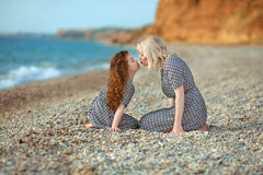 Mother kissing her daughter on the beach. outdoor family portrai Royalty Free Stock Photography