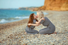 Mother kissing her daughter on the beach. outdoor family portrai Royalty Free Stock Image