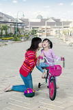Mother kissing her daughter on a bicycle Royalty Free Stock Image