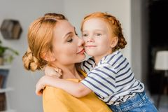 Mother kissing her daughter in cheek. Beautiful mother kissing her cute little daughter in cheek Stock Photography