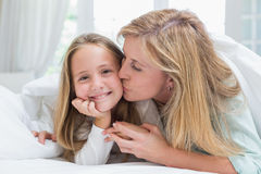 Mother kissing her daughter on the cheek in the bed Stock Photos