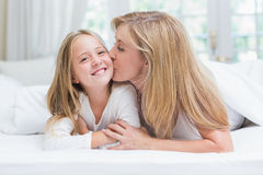 Mother kissing her daughter on the cheek in the bed. At home in the bedroom Stock Photography