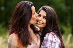Mother kissing her daughter on the cheek Royalty Free Stock Photo