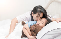 Mother is kissing her daughter in cheek while laying on bed Royalty Free Stock Photography