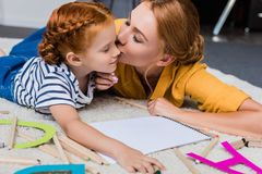 Mother kissing her daughter in cheek. Mother kissing her cute little daughter in cheek on floor at home Stock Photos