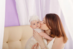 Mother kissing her daughter on cheek. Stock Photo
