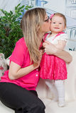 Mother kissing her daughter Stock Photos