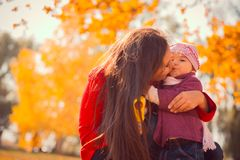 Mother kissing her daughter in the park Royalty Free Stock Photography