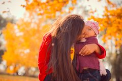 Mother kissing her daughter in the park Stock Image