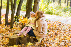 Mother kissing her daughter in the park.  Woman Royalty Free Stock Photos