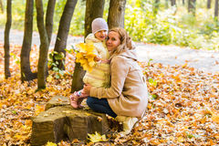 Mother kissing her daughter in the park.  Woman Stock Photo