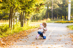 Mother kissing her daughter in the park. Woman with child on autumn forest Royalty Free Stock Photography