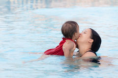 Mother kissing her daughter in pool Royalty Free Stock Photos
