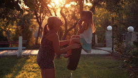 Mother kissing her daughter and ride on a swing. Mother tender kissing her small daughter and ride on a swing on backyard at home, in foreground and sunlight Royalty Free Stock Photo