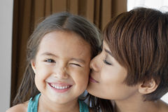 Mother kissing her daughter' s cheek Stock Photos