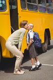 Mother kissing her daughter by school bus Royalty Free Stock Photography
