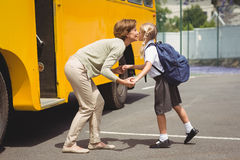 Mother kissing her daughter by school bus Stock Photography