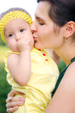 Mother kissing her daughter. Mother tenderly kisses her daughter on the cheek stock photo