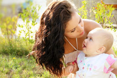 Mother kissing her dear baby, outdoors portrait Stock Photo